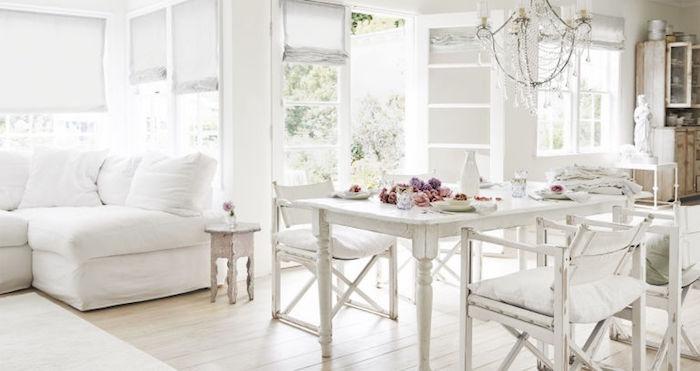 intérieur tout en blanc, parquet clair, canapé blanc, table et chaises blanches usées, lustre baroque, decoration de fleurs colorées sur al table