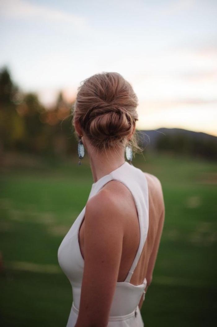 idée de chignon facile mariage a faire soi meme, coiffure cheveux long, robe blanche, boucles d oreille bleues, coiffure femme élégante