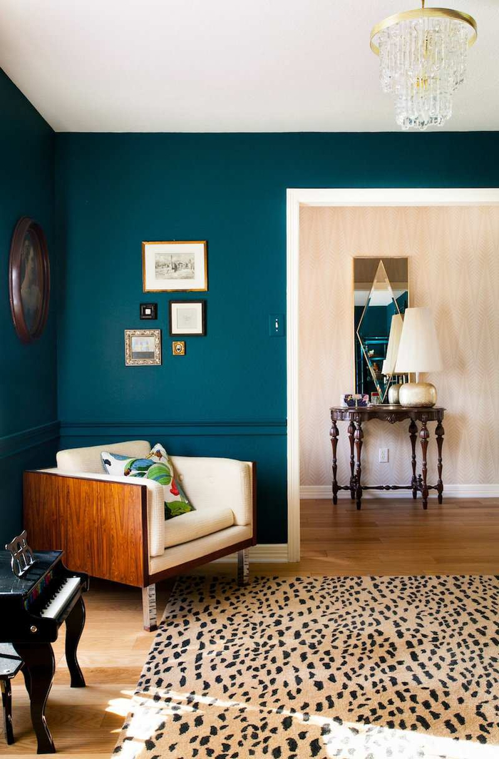 salon aux murs bleu paon foncé en contraste avec le canapé neige et le tapis imprimé à motif animalier