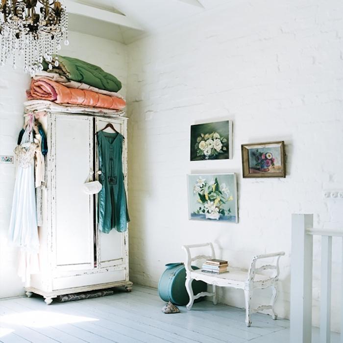 chambre shabby chic femme, parquet blanc, mur-de-briques blanchies, armoire blanche patinée, robes multicolores, lustre élégant