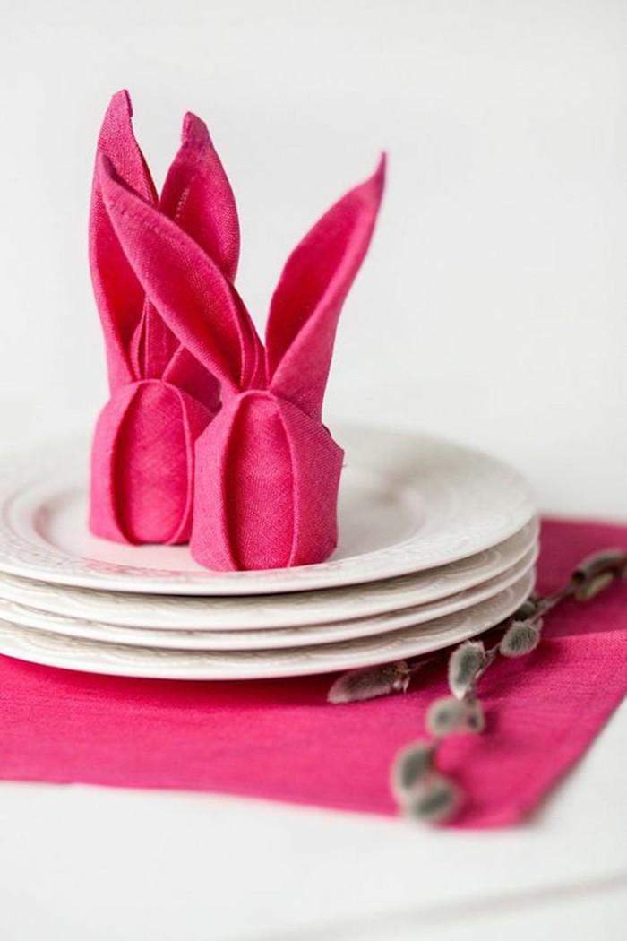 technique origami, pliage de serviette en tissu rose, serviette en forme de lapin, déco de table pâques