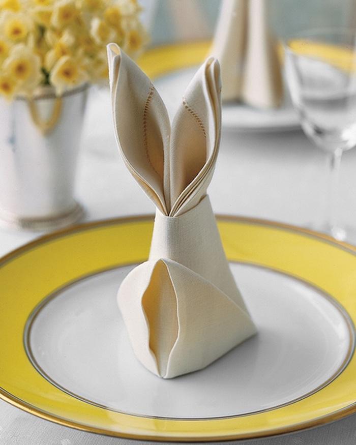 pliage de serviette en forme de lapin, idée déco de table pour paques en jaune et blanc