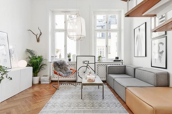 appartement scandinave, tapis en blanc et gris à motifs triangulaires, chaise orange avec housse en faux fur, cornes en bois