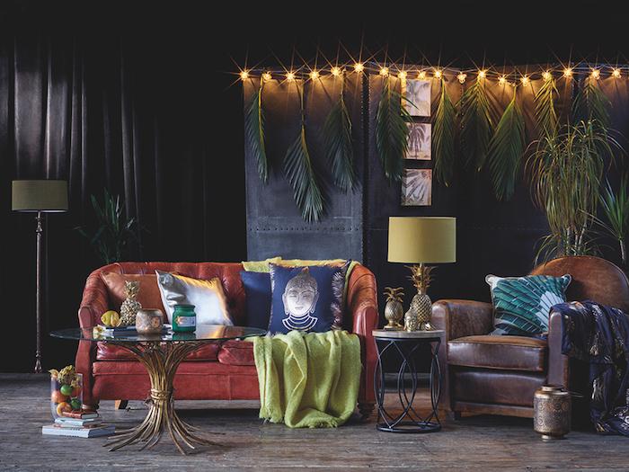 motif tribal, rideaux longs en noir, guirlande lumineuse avec feuilles vertes tropicales, coussins à imprimé bouddhisme, lampe jaune à motif ananas