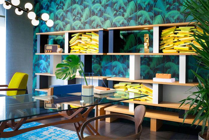 papier peint tropical, revêtement de sol en bois marron, étagères murales en bois peint en bleu, bureau en verre avec pieds en bois