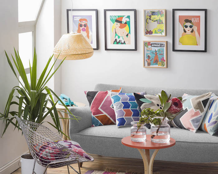 canapé velours, murs peints en blanc avec cadres photo noirs, plantes vertes tropicales, coussins décoratifs à motifs géométriques