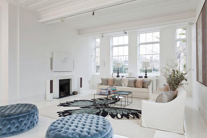 dessin de papillon, tabouret bas en velours bleu, canapé blanc avec coussins, tapis blanc à motif grand papillon