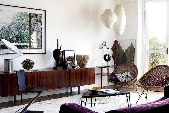 motif tribal, salon aux murs blancs, chaise en rotin avec coussins à motifs ethniques, canapé en velours violet, peinture nature