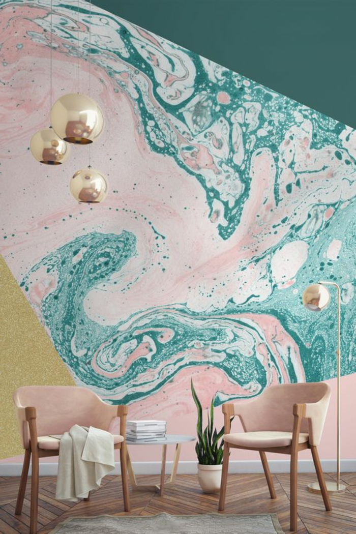 decortion scandinave dans un salon moderne, mur couleur vert d eau et rose poudré, suspensions boules dorées, chaise en bois, coussins de chaise rose, parquet marron, tapis gris