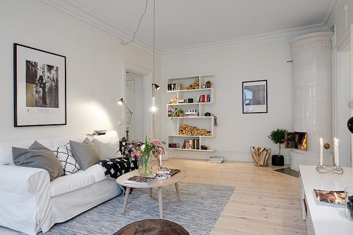 appartement scandinave, table basse en bois, bougies allumées, cheminée blanche de coin, parquet en bois