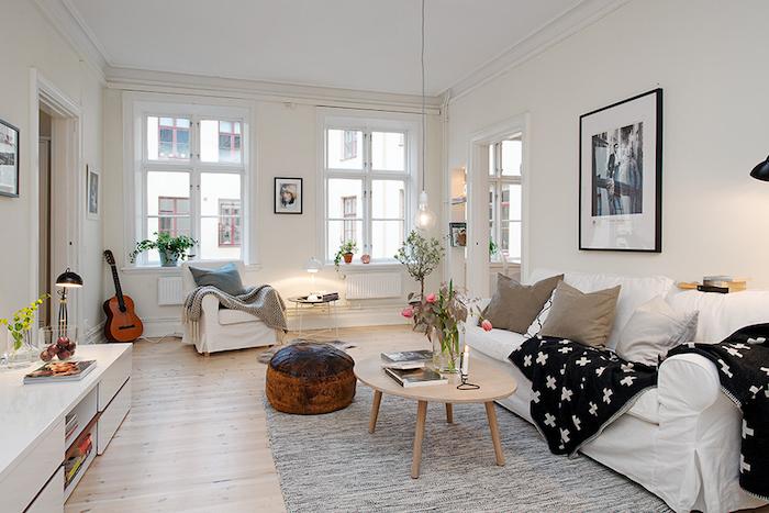 deco scandinave salon, canapé blanc avec coussins marron, parquet en bois clair, plantes vertes, pouf en cuir marron