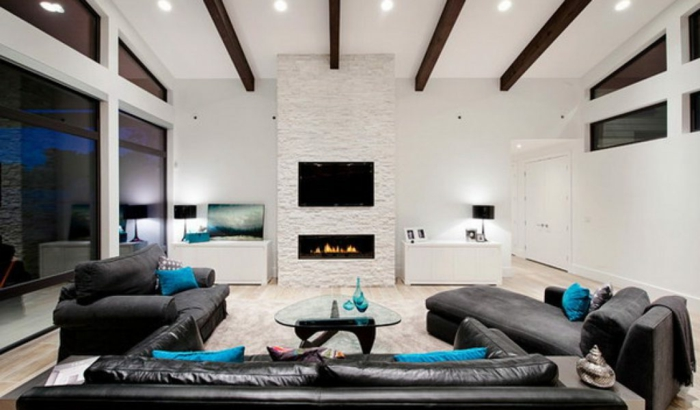 deco salon contemporain, sofas en cur noir et coussins bleus, poutres apparentes sur un plafond blanc