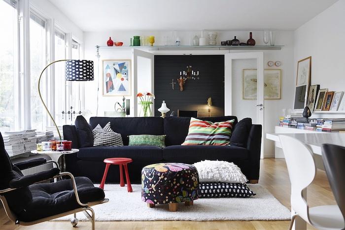 mobilier scandinave, parquet de bois, plafond blanc, canapé en tissu noir avec coussins décoratifs multicolore, cadres photos en bois