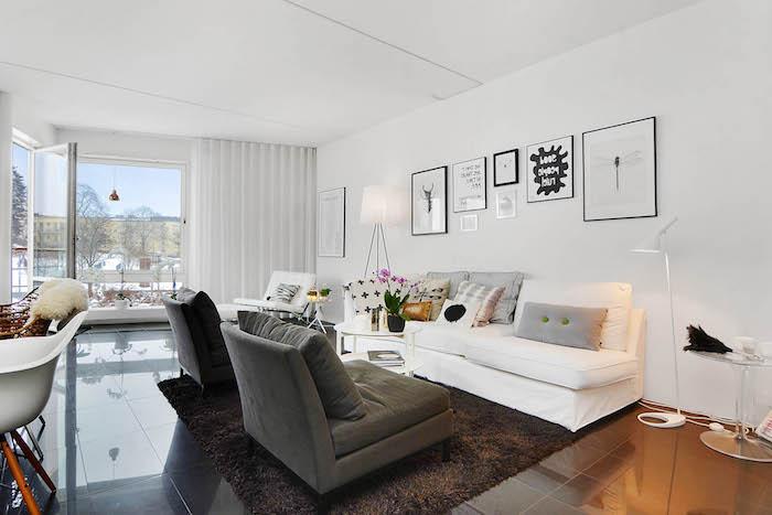 tapis scandinave, grandes fenêtres, murs peints en blanc, canapé blanc avec coussins décoratifs, lampe sur pied blanche