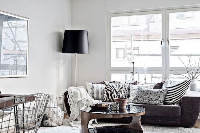 meuble scandinave, grande lampe sur pied en noir, canapé en tissu marron, coussins en blanc et noir, table en verre et bois