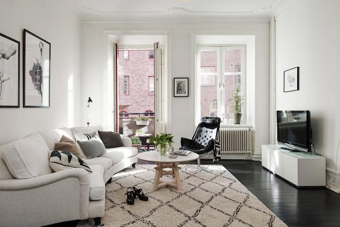 style scandinave, murs peints en blanc, plafond blanc avec décoration en plâtre, chaise noire avec plaid en blanc et noir
