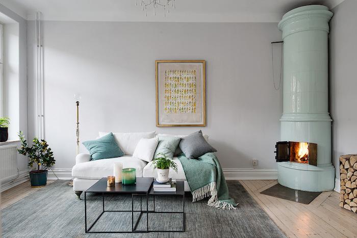 style scandinave, canapé blanc avec coussins décoratifs, cheminée verte de coin, parquet en bois, table basse en noir