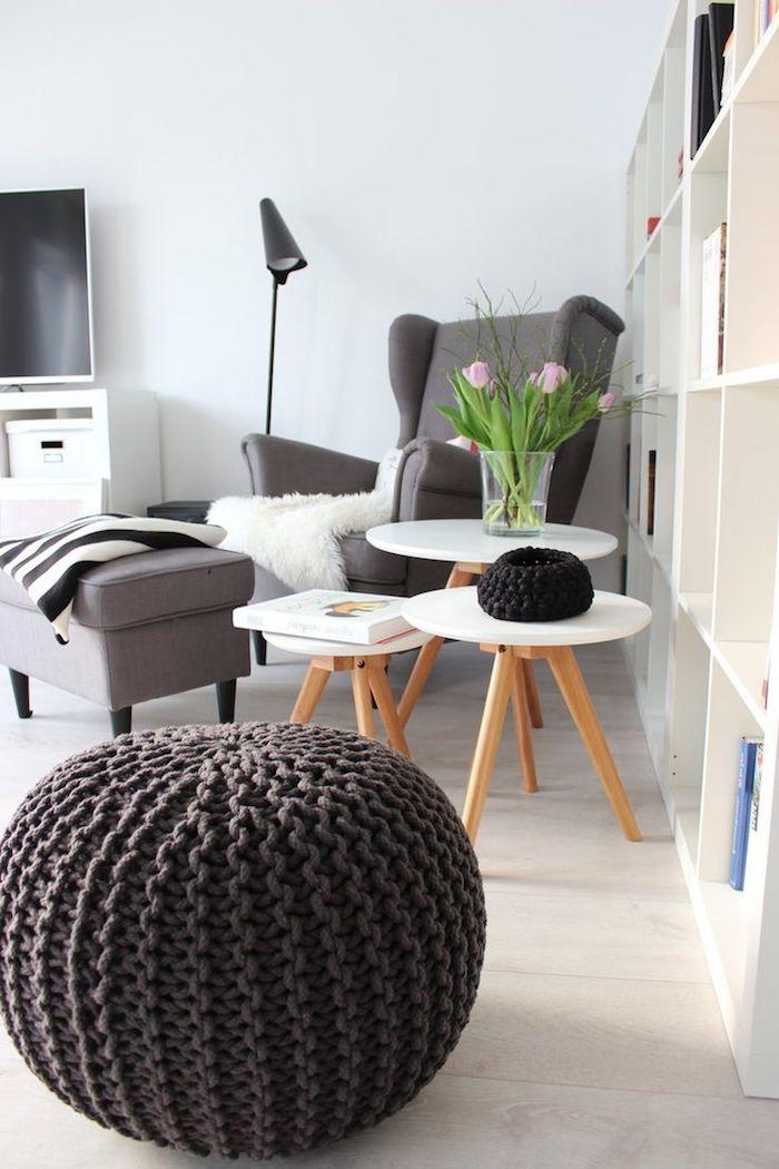 mobilier scandinave, murs peints en blanc, fauteuil en gris foncé avec housse en faux fur, pouf marron en crochet