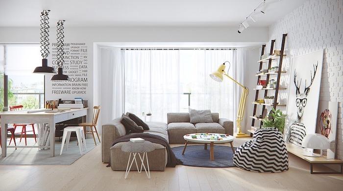 style scandinave, pouf rayé en blanc et noir, tapis rond en bleu, lampe sur pied en jaune, canapé d'angle en beige foncé