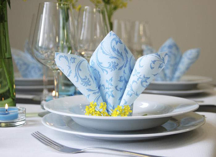 technique origami avec serviette en papier, arrangement de table en blanc et bleu, serviette en papier bleue