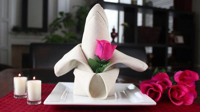 atmosphère romantique, nappe de table rouge, bougies blanches, pliage de serviette originale
