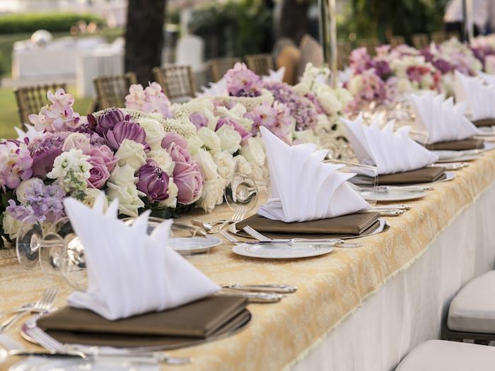 arrangement de table mariage, nappe beige à motifs dorés, bouquets de roses, serviette origami blanche