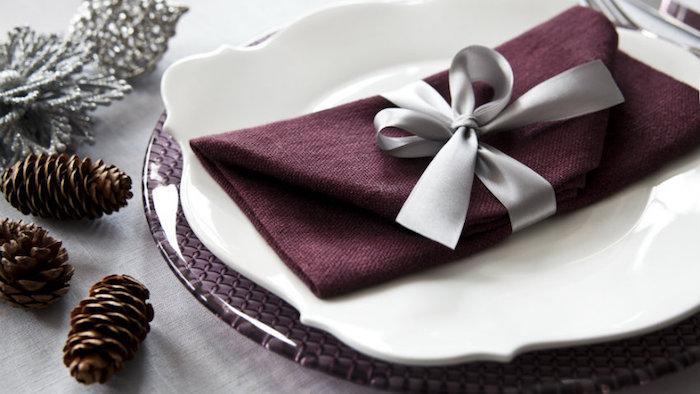 arrangement de table de noel, petites pommes de pin, décoration florale en argent, pliage de serviette