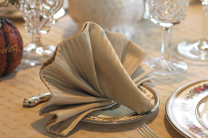 nappe de table beige, pliage de serviette élégant, arrangement de table, service à motifs floraux
