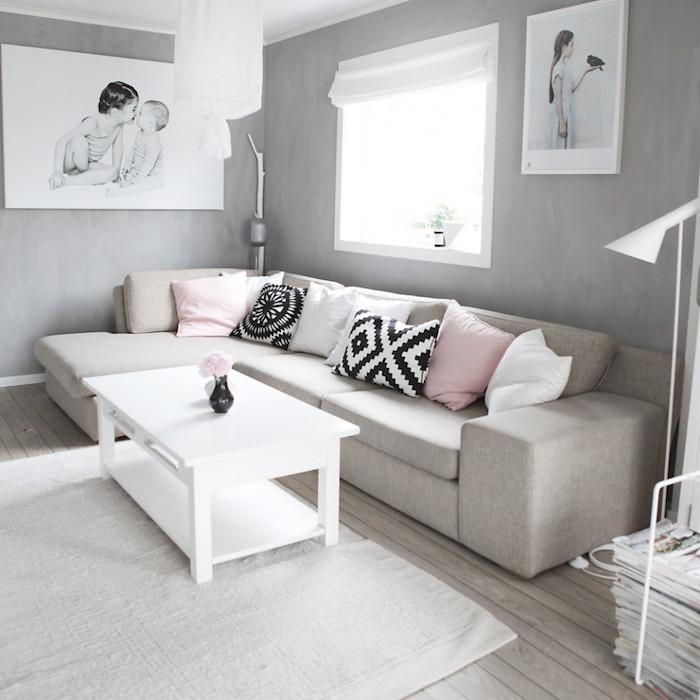 mobilier scandinave, suspension luminaire blanche, murs peints en gris, canapé d'angle beige avec coussins décoratifs, table blanche