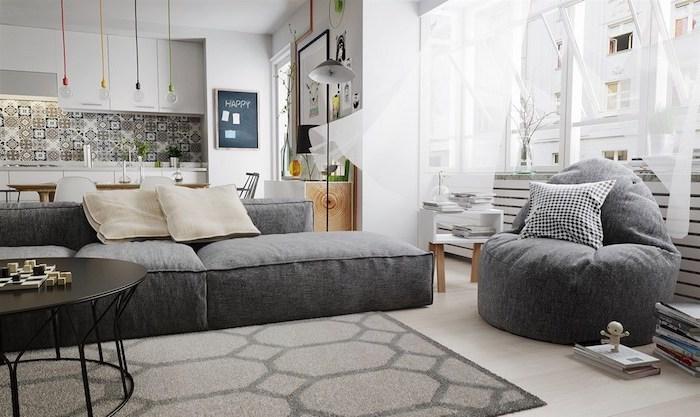 inspiration scandinave, cuisine ouverte au salon, table ronde en noir, pouf en gris avec coussin en blanc et noir