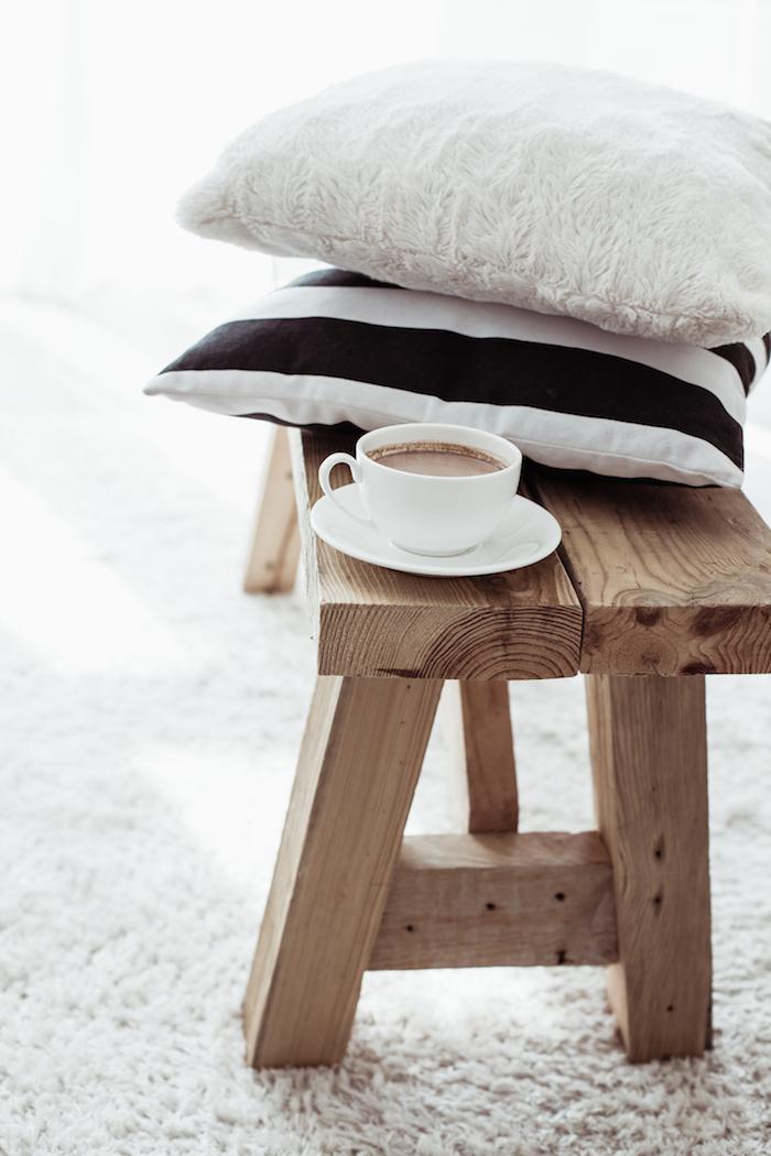 intérieur scandinave, table basse en bois, tasse de café, coussins décoratifs en blanc et noir, tapis moelleux en blanc