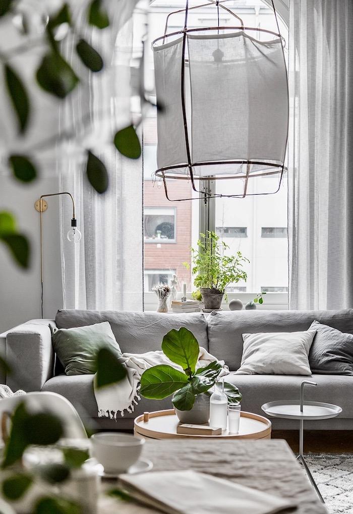 deco salon style scandinave, tapis à motifs géométriques en beige, canapé en tissu gris avec coussins décoratifs