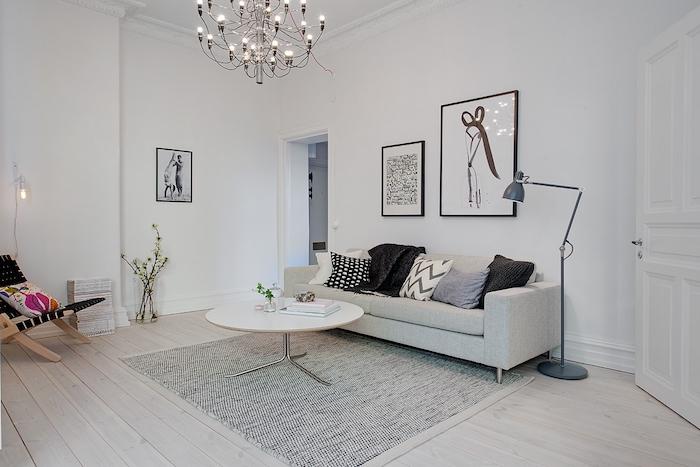 deco nordique, table basse en blanc, lampe sur pied en gris, parquet de bois clair, cadres photo noirs, fleurs vertes