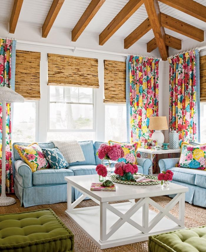 style shabby chic comment faire, canapé shabby chic bleu, coussins et rideaux fleuris, tapis marron, table basse blanche, poutres apparentes, bouquets de fleurs