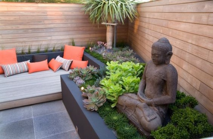 déco de jardin zen, carré végétalisé avec des succulents, palmier, canapé avec des coussins orange, dalles de pierre, cloture en bois