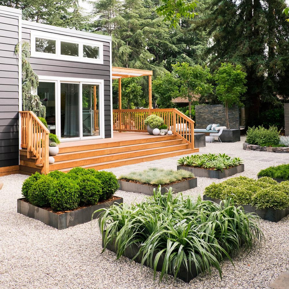 déco de jardin zen, gravier sur le sol, petits carrés végétalisés, maison ultra moderne dans un cadre naturel espace détente au fond