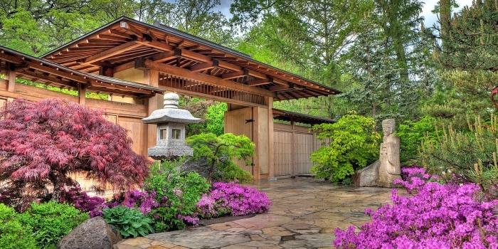 entrée arc japonais, espace, recouvert de dalles de pierre, entouré de vegetation verte et e fleurs, lanterne et statue japonaise