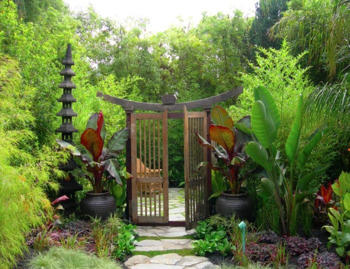 decoration zen de chemin de pierres, arbustes et bambou avec des vases des deux cotés d une porche cochère japonaise