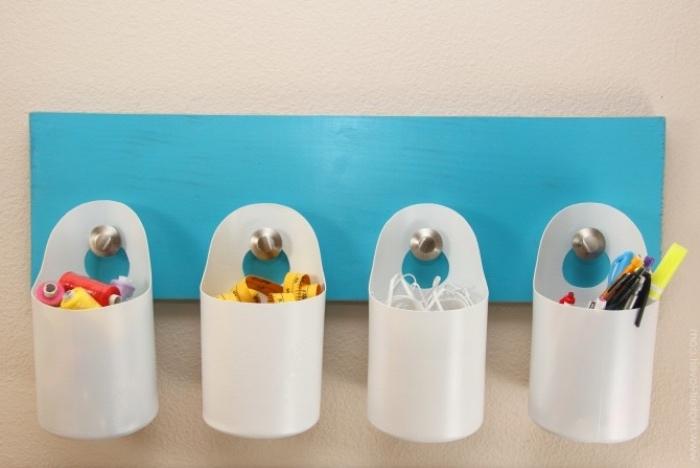 idée rangement, contenants en plastique blancs sur une planche repeinte en bleu, accrochés à une patère, idée organisateur mural simple