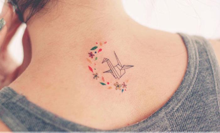 un petit tatouage minimaliste à la nuque mêlant des motifs floraux et une grue en origami