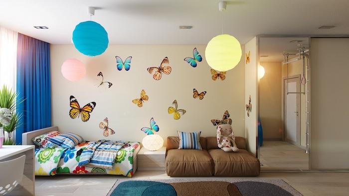 deco moderne, aménagement chambre d'enfant, rideaux longs en bleu, couverture de lit multicolore, dessins papillon sur les murs