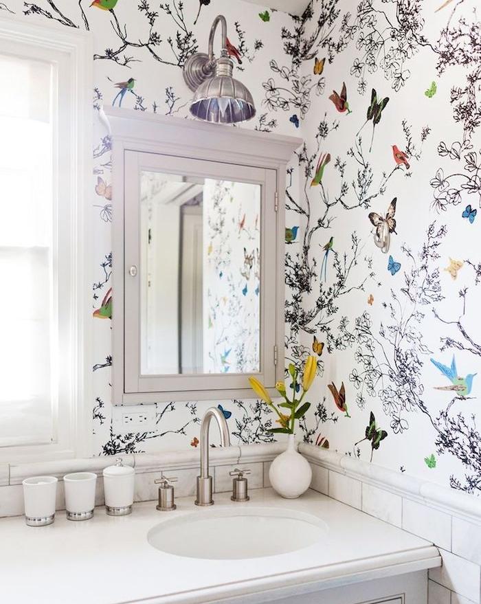 déco appartement, lavabo blanche, vase blanche avec fleurs oranges, miroir rectangulaire, papier peint à papillons