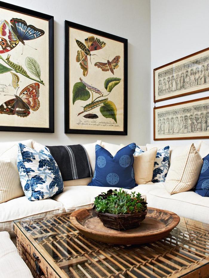 tissu tropical, salon aux murs blancs, coussins décoratifs bleus, canapé d'angle beige, plant verte, peinture papillon aux cadres noirs