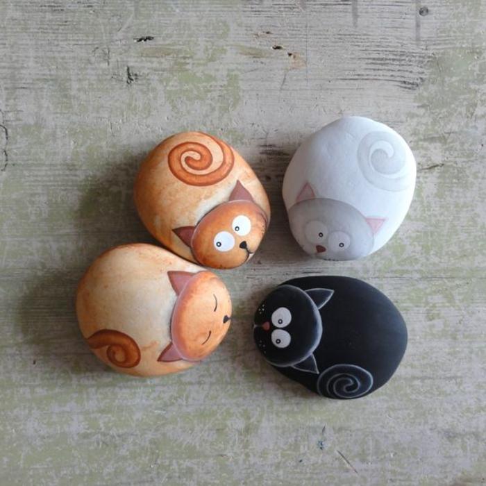 des chats adorables dessinés sur des galets arrondis, une activité créative