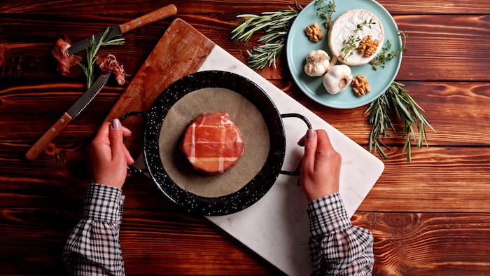 envelopper le brie des tranches de prosciutto et placer sur une feuille de papier de cuisson pour enfourner idée recette brie au four cuit pour l entrée originale