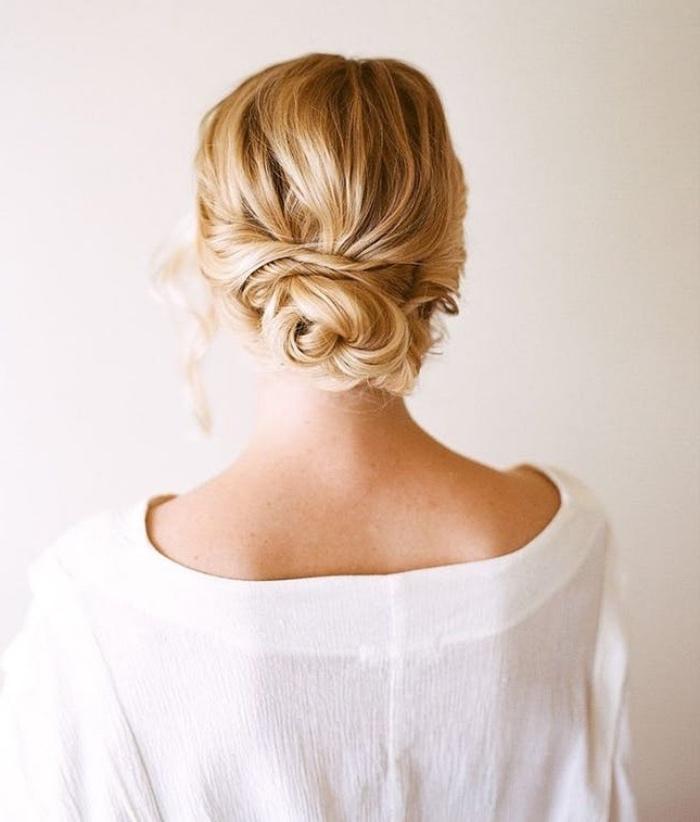 chignon bas facile et élégant sur des cheveux longs blond, mèches tombante de coté, cheveux ondulés