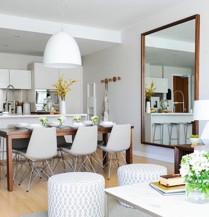 idée pour aménager une petite cuisine blanche, intérieur tout en blanc, salle à manger avec table en bois brut et chaises design, parquet clair, coin salon avec tabourets blanc et gris et tapis gris, table basse plateau aspect marbre, grande miroir
