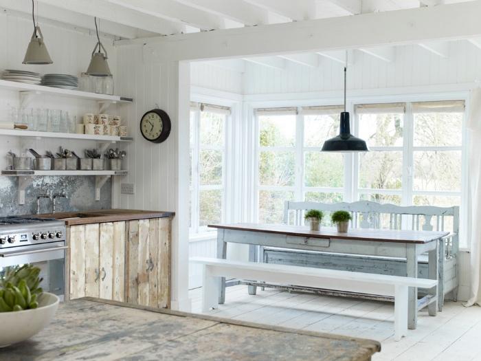 façade cuisine et table en bois brut, étageres blanches et vaisselle vintage, suspensions industrielles, coin repas table et bancs blancs, parquet blanchi