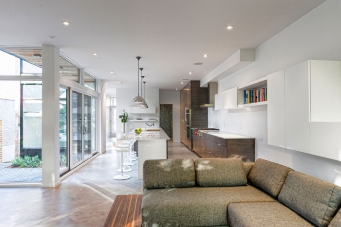 idée cuisine ouverte sur le salon, façade cuisine en bois marron, revêtement sol gris, bar avec des chaises blanches, éclairage lampes au dessus, canapé d angle gris