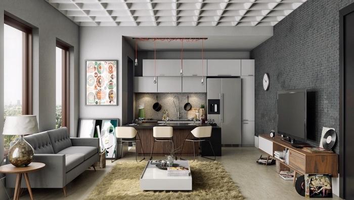 modèle de cuisine américaine avec façade grise, bar en bois avec des chaises, canapé gris, tapis beige, table basse blanche, meuble tv en bois, suspensions ampoules